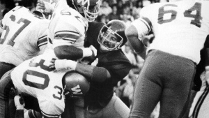 Toronto Argonauts' Jim Stillwagon (centre) holds up a wall of Winnipeg Blue Bombers to stop ball carrier John Bledsoe (30) during CFL action in Toronto on July 10, 1974. Stillwagon, who helped Ohio State win two U.S. college football titles before playing five seasons with the CFL's Toronto Argonauts, has died at the age of 68. THE CANADIAN PRESS/Staff