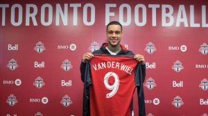 Toronto FC's new signing Gregory van der Wiel poses for a photo with a TFC shirt following a news conference in Toronto on Monday,February 5, 2018. THE CANADIAN PRESS/Chris Young