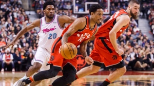 Toronto Raptors DeMar DeRozan goes to the basket with teammate Jonas Valanciunas, right, against Miami Heat Justise Winslow, left, during the first half of NBA basketball action in Toronto, Tuesday February 13, 2018. THE CANADIAN PRESS/Mark Blinch