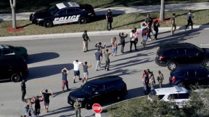 Students hold their hands in the air as they are evacuated by police from Marjory Stoneman Douglas High School in Parkland, Fla., on Wednesday, Feb. 14, 2018, after a shooter opened fire on the campus. (Mike Stocker/South Florida Sun-Sentinel via AP)