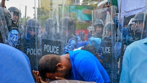 In this photo taken Friday, Feb. 16, 2018, policemen use pepper spray to disperse pro-opposition supporters during a protest in Male, Maldives. Dozens of pro-opposition supporters have been injured and many were arrested after police in the Maldives broke up countrywide protests demanding the resignation of President Yameen Abdul Gayoom and the release of his political opponents from prison. (AP Photo/Mohamed Sharuhan)