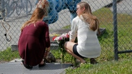Jessica Gargaro, 15, left, and Sarah Goodchild, 15, both students at Marjory Stoneman Douglas High School, place flowers outside the school on Sunday, Feb. 18, 2018, in Parkland, Fla. Authorities opened the streets around the school, which had been closed since a mass shooting on Wednesday. Nikolas Cruz, a former student, was charged with 17 counts of premeditated murder. (AP Photo/Gerald Herbert)