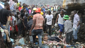 Rescuers recover a body as they search for survivors at the collapse of a garbage mound in Maputo, Mozambique, Monday, Feb. 19, 2018. Mozambican media say at least 17 people died when heavy rains triggered the partial collapse of the mound garbage. (AP Photo/Ferhat Momade)