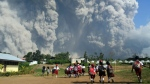 School children walk as Mount Sinabung erupts in Karo, North Sumatra, Indonesia, Monday, Feb. 19, 2018. Rumbling Mount Sinabung on the Indonesian island of Sumatra has shot billowing columns of ash more than 5,000 meters (16,400 feet) into the atmosphere and hot clouds down its slopes. The volcano, one of three currently erupting in Indonesia, was dormant for four centuries before exploding in 2010.(AP Photo/Sarianto)