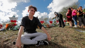 Chris Grady, a student at Marjory Stoneman Douglas High School, poses at a memorial outside the school, for Wednesday's mass shooting, in Parkland, Fla., Monday, Feb. 19, 2018.  (AP Photo/Gerald Herbert)