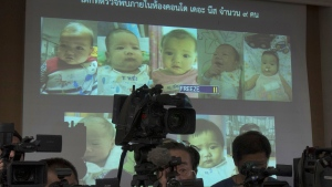FILE - In this Aug. 12, 2014, file photo, the media attend a press briefing where Thai police display projected pictures of surrogate babies born to a Japanese man who is at the center of a surrogacy scandal during a press conference at the police headquarters in Chonburi, Thailand.  (AP Photo/Sakchai Lalit, File)