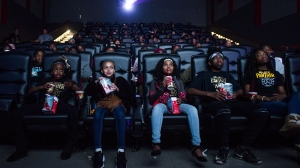 "Mari Copeny, third from left, watches a free screening of the film ""Black Panther"" with more than 150 children, after she raised $16,000 to provide free tickets in an entire theater on Monday, Feb. 19, 2018 in Flint Township, Mich. As ""Black Panther"" debuts in theaters across the U.S., educators, philanthropist, celebrities and business owners are pulling together their resources to bring children of color to see the film that features a black superhero in a fictional, un-colonized African nation. (Jake May /The Flint Journal-MLive.com via AP)"