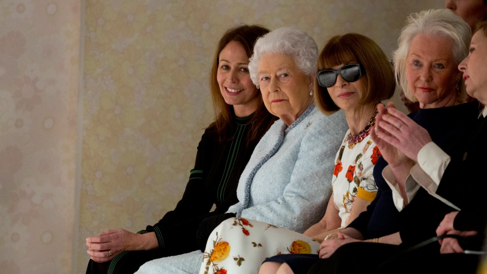 Britain's Queen Elizabeth, second left, sits next to fashion editor Anna Wintour, third left, and Caroline Rush, chief executive of the British Fashion Council (BFC) as they view Richard Quinn's runway show before presenting him with the inaugural Queen Elizabeth II Award for British Design, as she visits London Fashion Week's BFC Show Space in central London, Tuesday, Feb. 20, 2018. (Isabel Infantes/PA via AP)