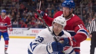 Montreal Canadiens' Peter Holland, right, grabs Toronto Maple Leafs' Eric Fehr during first period NHL pre-season action Wednesday, September 27, 2017 in Quebec City. THE CANADIAN PRESS/Jacques Boissinot