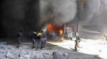 In this photo released on Tuesday Feb. 20, 2018 provided by the Syrian Civil Defense group known as the White Helmets, shows members of the Syrian Civil Defense extinguishing a store during airstrikes and shelling by Syrian government forces, in Ghouta, a suburb of Damascus, Syria. Intense Syrian government shelling and airstrikes of rebel-held Damascus suburbs killed at least 100 people since Monday in what was the deadliest day in the area in three years, a monitoring group and paramedics said Tuesday. (Syrian Civil Defense White Helmets via AP)