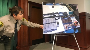 Deputy Lisa Jansen displays photos of weapons and ammo at a news conference in Los Angeles on Wednesday, Feb. 21, 2018. (AP Photo/Mike Balsamo)