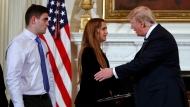 President Donald Trump greets Julia Cordover, the student body president at Marjory Stoneman Douglas High School in Parkland, Fla.,, as fellow student Jonathan Blank watches at a listening session with high school students and teachers in the State Dining Room of the White House in Washington, Wednesday, Feb. 21, 2018. (AP Photo/Carolyn Kaster)
