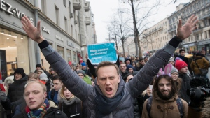 FILE - In this Sunday, Jan. 28, 2018 file photo, Russian opposition leader Alexei Navalny, centre, attends a rally in Moscow, Russia. Navalny, who is President Vladimir Putin's most visible and vehement foe, Russian opposition leader Alexei Navalny who has been barred from running in the next month's presidential election was detained by police on Thursday but released less than hour later. (AP Photo/Evgeny Feldman, File)