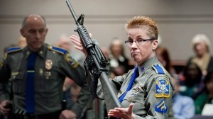 In this Jan. 28, 2013, file photo, firearms training unit Detective Barbara J. Mattson, of the Connecticut State Police, holds up a Bushmaster AR-15 rifle, the same make and model of gun used by Adam Lanza in the Sandy Hook School shooting, during a hearing of a legislative subcommittee in Hartford, Conn. Remington, the gunmaker beset by falling sales and lawsuits tied to the Sandy Hook Elementary School massacre, said Monday, Feb. 12, 2018, that it has reached a financing deal that would allow it to continue operating as it files for Chapter 11 bankruptcy protection. (AP Photo/Jessica Hill, File)
