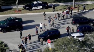 In this Wednesday, Feb. 14, 2018 file photo, students hold their hands in the air as they are evacuated by police from Marjory Stoneman Douglas High School in Parkland, Fla., after a shooter opened fire on the campus. A week after a shooter slaughtered more than a dozen people in the Florida high school, thousands of protesters, including many angry teenagers, swarmed into the state Capitol on Wednesday, Feb. 21, calling for changes to gun laws, a ban on assault-type weapons and improved care for the mentally ill. (Mike Stocker/South Florida Sun-Sentinel via AP, File)
