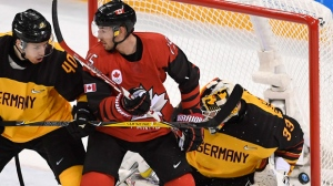 Canada forward Brandon Kozun (15)battles with Germany defenceman Bjorn Krupp (40) as Germany goaltender Danny Aus Den Birken (33) gives up a goal to Canada forward Derek Roy, not shown, in third period semifinal Olympic men's hockey action at the 2018 Olympic Winter Games in Gangneung, South Korea on Friday, February 23, 2018. THE CANADIAN PRESS/Nathan Denette