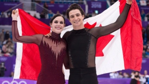 Ice dance gold medallists Canada's Tessa Virtue and Scott Moir hold up the Canadian flag during victory ceremonies at the Pyeongchang Winter Olympics Tuesday, February 20, 2018 in Gangneung, South Korea. THE CANADIAN PRESS/Paul Chiasson