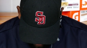 Cleveland Indians right fielder Abraham Almonte lowers his head as he wears a cap honoring the victims of the shooting at Marjory Stoneman Douglas High School prior to a spring training baseball game against the Cincinnati Reds Friday, Feb. 23, 2018, in Goodyear, Ariz. (AP Photo/Ross D. Franklin)