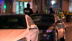 Officers are seen investigating after shots were fired at a vehicle on Queen Street West in the city's Parkdale neighbourhood on Friday evening.