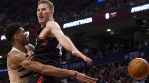 Milwaukee Bucks' Giannis Antetokounmpo (left) plays the ball around Toronto Raptors' Jakob Poeltl during second half NBA basketball action in Toronto on Friday February 23, 2018. THE CANADIAN PRESS/Chris Young