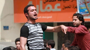 In this April 1, 2011 photo, activist Ahmed Douma, left, chants slogans as activist Khaled ElSayed, right, supports him, during a march to Tahrir Square demanding the prosecution of members of former President Hosni Mubarak's regime in Cairo, Egypt. Secular activist Ahmed Douma, 27, was one of the leading activists behind the country's Jan. 25-Feb. 11, 2011 uprising against autocrat Hosni Mubarak and was later a fierce critic of the Muslim Brotherhood during Morsi' rule. He was sentenced to life last year for taking part in clashes between protesters and security forces in late 2011. (AP Photo/Sarah Carr, File)
