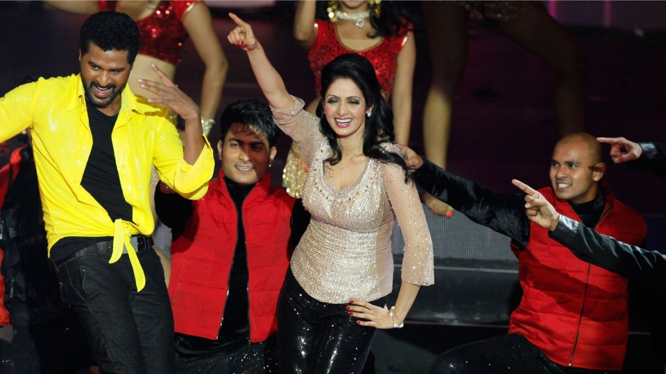 This July 6, 2013 file photo shows Bollywood actors Sridevi, center, and Prabhu Deva, left in yellow, performing during the International Indian Film Academy (IIFA) awards in Macau. (AP Photo/Kin Cheung, File)