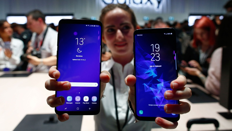 A woman holds the new Galaxy S9 and S9+ during the Samsung Galaxy Unpacked 2018 event on the eve of the Mobile World Congress wireless show, in Barcelona, Spain, Sunday, Feb. 25, 2018. Samsung unveiled new smartphones with largely unchanged designs and incremental improvements such as a better camera. (AP Photo/Manu Fernandez)