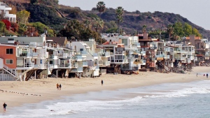 In this Dec. 20, 2015, file photo, waves roll up to and under homes perched over a sandy beach in Malibu, Calif. (AP Photo/John Antczak, file)