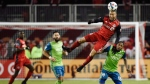 Toronto FC defender Justin Morrow (2) heads the ball over Seattle Sounders defender Kelvin Leerdam (18) during second half MLS Cup Final soccer action in Toronto on Saturday, December 9, 2017. THE CANADIAN PRESS/ Nathan Denette