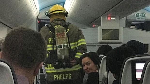 A firefighter is seen on board an Air Canada plane after a passenger's cellphone caught fire.
