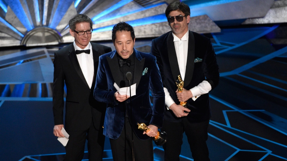 """Jeffrey A. Melvin, from left, Paul Denham Austerberry, and Shane Vieau accept the award for best production design for """"The Shape of Water"""" at the Oscars on Sunday, March 4, 2018, at the Dolby Theatre in Los Angeles. (Photo by Chris Pizzello/Invision/AP)"""