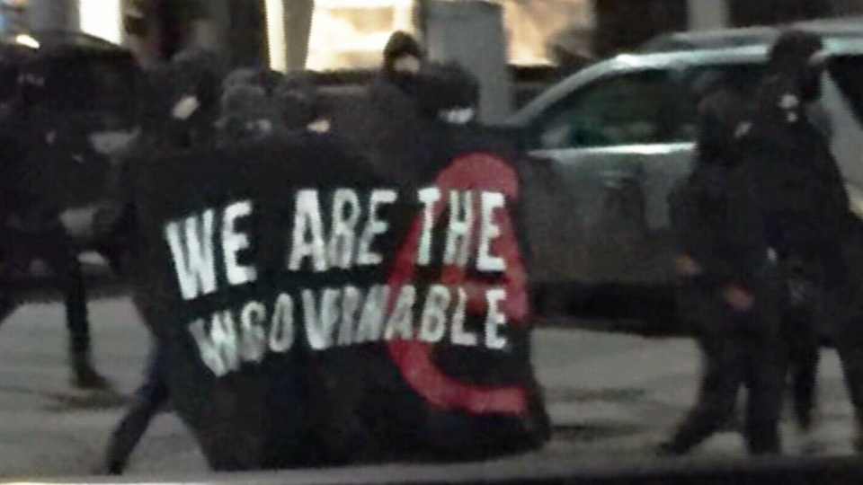"Masked individuals carrying a banner that says ""We Are the Ungovernables"" are seen on Locke Street in Hamilton on Mar. 3, 2018. (CTV News Toronto)"