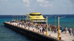 Tourists and passengers disembark from a ferry on to the wharf on Playa del Carmen, Mexico, Friday, March 2, 2018. Undetonated explosives were found on another ferry that runs between the Caribbean resorts of Playa del Carmen and the island of Cozumel, authorities said, less than two weeks after a blast shook another ferry plying the same route. (AP Photo/Gabriel Alcocer)