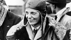 """In a June 26, 1928 file photo, American aviatrix Amelia Earhart poses with flowers as she arrives in Southampton, England, after her transatlantic flight on the """"Friendship"""" from Burry Point, Wales. (AP Photo, File)"""