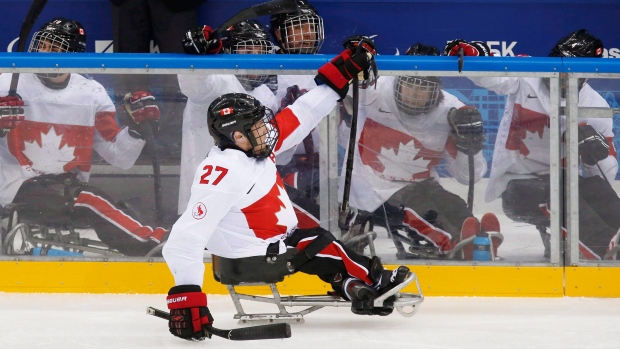 78a8646554a Canada s Brad Bowden celebrates with teammates after Canada s goal during  an ice sledge hockey match between Canada and Czech Republic at the 2014  Winter ...