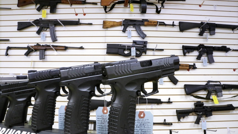 In this Jan. 16, 2013, file photo, assault weapons and hand guns are seen for sale at Capitol City Arms Supply in Springfield, Ill. (AP Photo/Seth Perlman, file)