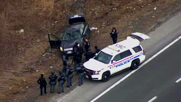 Police officers are seen searching for multiple suspects after a shots were fired at a bank robbery in Durham Region.
