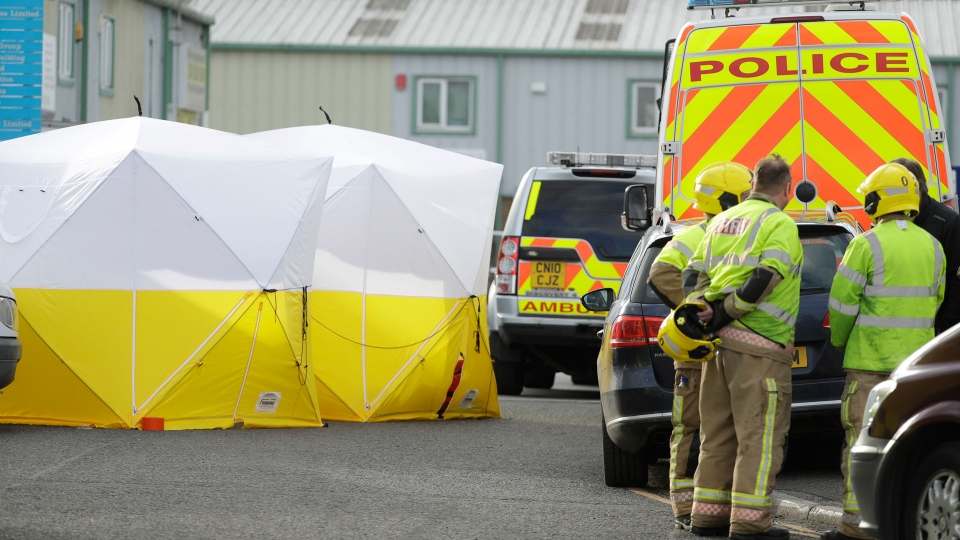"Fire officers stand inside a cordon at the vehicle recovery business ""Ashley Wood Recovery"" in Salisbury, England, Tuesday, March 13, 2018. The use of Russian-developed nerve agent Novichok to poison former-spy Sergei Skripal and his daughter Yulia makes it ""highly likely"" that Russia was involved, British Prime Minister Theresa May said Monday. Novichok refers to a class of nerve agents developed in the Soviet Union near the end of the Cold War. AP Photo/Matt Dunham)"