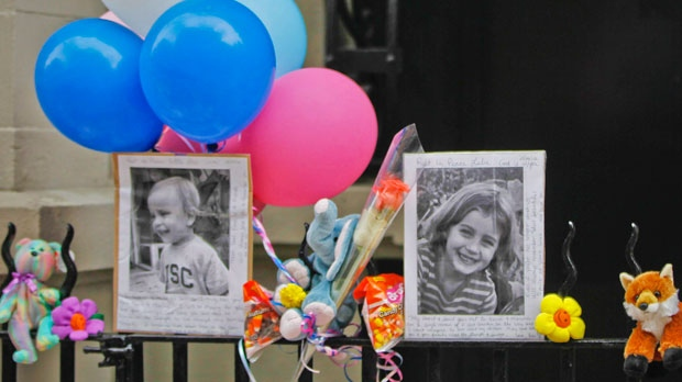 In this Oct. 27, 2012, file photo, photographs of 6-year-old Lucia Krim and her 2-year-old brother, Leo, are displayed alongside balloons and stuffed animals at a memorial outside the apartment building where they lived in New York. Opening arguments begin Thursday, March 1, 2018, for Yoselyn Ortega, the family's nanny charged with murder in the Oct. 25, 2012, deaths of the siblings. (AP Photo/Mary Altaffer, File)