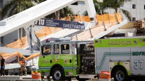 Emergency personnel responds to a collapsed pedestrian bridge connecting Florida International University Florida International on Thursday, March 15, 2018 in the Miami area. The brand-new pedestrian bridge collapsed onto a highway crushing at least five vehicles. Several people were seen being loaded into ambulances and authorities said they were searching for people. (Daniel A. Varela/The Miami Herald via AP)