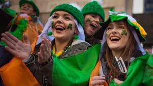 Spectators watch as revelers march up Fifth Avenue during the St. Patrick's Day Parade, Friday, March 17, 2017, in New York. New York City was awash in green and Irish pride Friday as throngs from both sides of the pond celebrated at the annual St. Patrick's Day Parade. (AP Photo/Andres Kudacki)