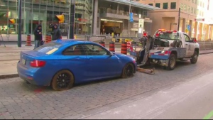A car is towed away from a streetcar tunnel at Queens Quay and Bay Street after a driver ventured into the tunnel and got stuck.
