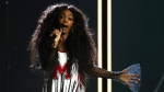 """In this Jan. 28, 2018 file photo, Sza performs """"Broken Clocks"""" at the 60th annual Grammy Awards at Madison Square Garden in New York.  SZA didn't let a torn ligament in her foot slow her down at a concert for her feverish fans in New York City. She walked into the venue Friday, March 16 with a crutch helping her to the chair placed in the middle of the stage for her comfort. She injured her foot while performing last week at the BUKU Music + Art Project festival in New Orleans.(Photo by Matt Sayles/Invision/AP, File)"""