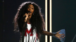 "In this Jan. 28, 2018 file photo, Sza performs ""Broken Clocks"" at the 60th annual Grammy Awards at Madison Square Garden in New York.  SZA didn't let a torn ligament in her foot slow her down at a concert for her feverish fans in New York City. She walked into the venue Friday, March 16 with a crutch helping her to the chair placed in the middle of the stage for her comfort. She injured her foot while performing last week at the BUKU Music + Art Project festival in New Orleans.(Photo by Matt Sayles/Invision/AP, File)"