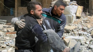 This photo released by the Syrian Civil Defense White Helmets, which has been authenticated based on its contents and other AP reporting, shows members of the White Helmets carrying a man who was wounded after airstrikes and shelling hit in Arbeen, in the eastern Ghouta region near Damascus, Syria, Tuesday, March. 20, 2018. (Syrian Civil Defense White Helmets via AP)