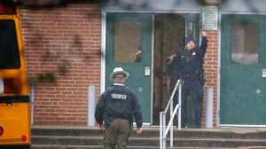A policeman gives a thumbs-up after moving students into a different area of Great Mills High School, the scene of a shooting, Tuesday morning, March 20, 2018 in Great Mills, Md.  (AP Photo/Alex Brandon)