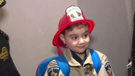 Matteo Papa tries on his new fire gear at his Woodbridge home.