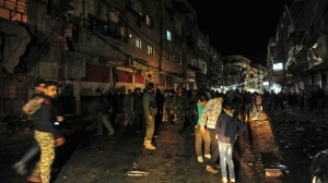 In this photo released on Tuesday, March 20, 2018 by the Syrian official news agency SANA, shows Syrian gathering at the site of a deadly mortar assault on a market in the Kashkol neighborhood of Damascus, Syria. The death toll from a rebel mortar assault on a market in Damascus has risen to over 40, according to state media, making it one of the deadliest attacks in the capital since the start of the seven-year civil war. (SANA via AP)