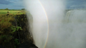 "In this April 1995, file photo, a rainbow forms in a cloud of mist over the Victoria Falls, Zimbabwe. The blockbuster film ""Black Panther"" has created a new compelling vision of Africa as a continent of smart, technologically savvy people with cool clothes living in a futuristic city amid stunning landscapes. (AP Photo/John Moore, File)"