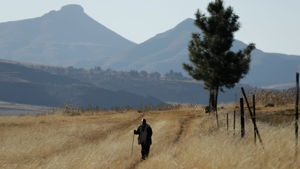 "In this June 3, 2017, file photo, a man walks on the land at Ha Mampho village, Lesotho. The blockbuster film ""Black Panther"" has created a new compelling vision of Africa as a continent of smart, technologically savvy people with cool clothes living in a futuristic city amid stunning landscapes. (AP Photo/Themba Hadebe, File)"